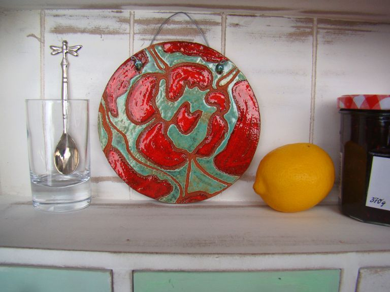 Charles Rennie Mackintosh inspired wall hanging.  A red glazed Rennie Mackintosh inspired flower design on glazed green background.  The tile is 13 cm in diameter the wire hanging fixing at the top of the tile is approx 2.5 cm.
